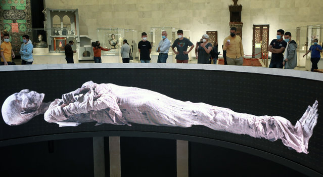 Visitors look at large displays of mummies in the National Museum of Egyptian Civilization after its reopening in Old Cairo, Egypt, 05 April 2021. The museum reopened a day after a parade, called The Pharaohs' Golden Parade, with 22 ancient Egyptian royal mummies – 18 kings and four queens – transferred from the Egyptian Museum at Tahrir Square to their new resting place at the National Museum of Egyptian Civilization in Fustat on 03 April 2021. The mummies will be put on display to the general public in the museum's Royal Hall of Mummies from 18 April 2021 on. (Photo by Khaled Elfiqi/EPA/EFE)