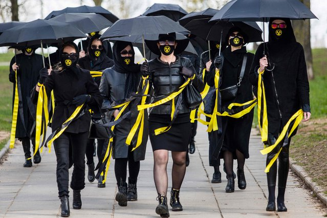 Women wearing black clothing and face masks with radioactivity sign march under umbrellas in Minsk, on April 26, 2021, to commemorate the victims of the Chernobyl nuclear disaster on the 35th anniversary of the tragedy. (Photo by AFP Photo/Stringer)