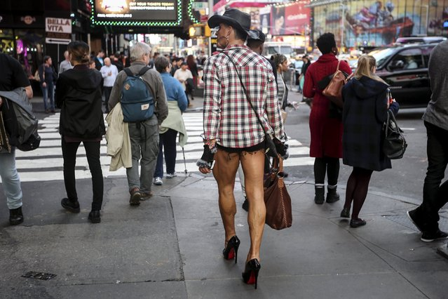 A man walks though Times Square in high heels during unseasonably warm weather on Christmas Eve in the Manhattan borough of New York December 24, 2015. (Photo by Carlo Allegri/Reuters)