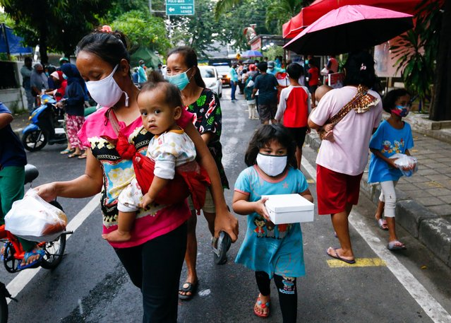 People wearing protective masks receive a free meal to break the fast during the holy fasting month of Ramadan amid the coronavirus disease (COVID-19) pandemic in Jakarta, Indonesia, April 15, 2021. (Photo by Ajeng Dinar Ulfiana/Reuters)