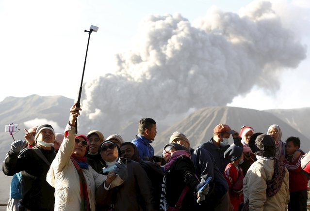 Tourists gather for a group photo as Mount Bromo erupts in the background near Ngadisari, Probolinggo, East Java, Indonesia January 6, 2016. (Photo by Darren Whiteside/Reuters)