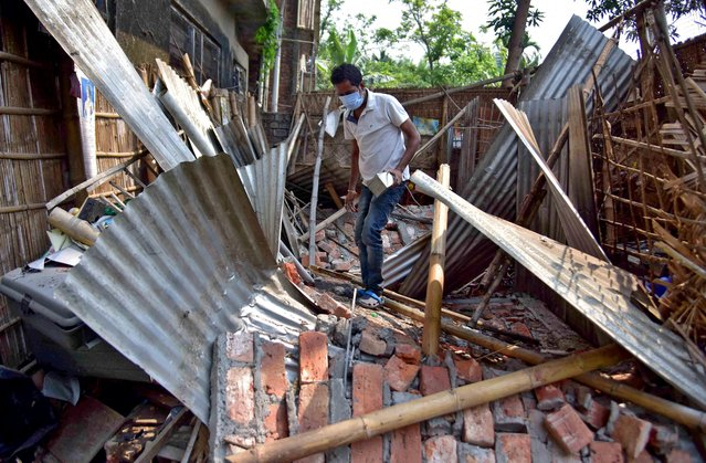 A man searches for his belongings amidst the debris after a boundary wall of his house collapsed following an earthquake in Nagaon district in the northeastern state of Assam, India, April 28, 2021. (Photo by Anuwar Hazarika/Reuters)