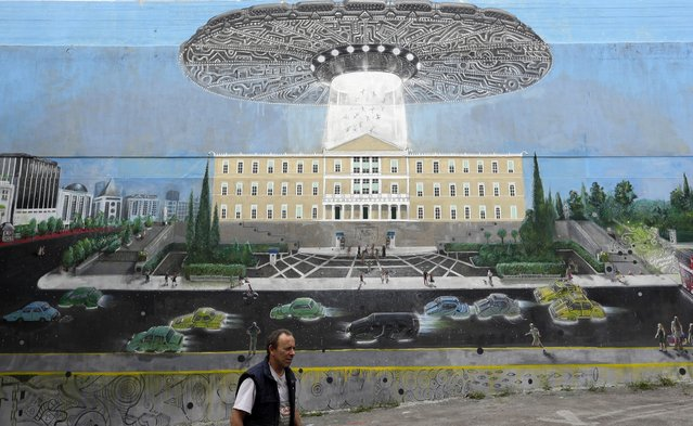 A car mechanic walks past a mural on the side of an office block depicting a flying saucer hovering over the Greek Parliament, in Athens, Monday, November 7, 2016. Greece's left-wing government has promised to swiftly impose a new series of sweeping cost cutting reforms by early next month as part of its international bailout, hoping to secure an agreement for debt relief from Eurozone lenders. (Photo by Thanassis Stavrakis/AP Photo)
