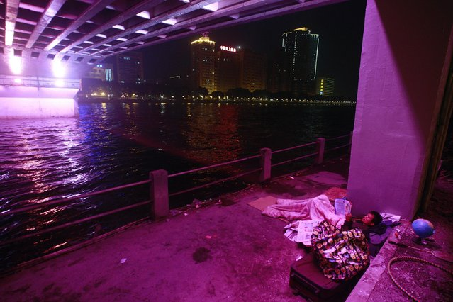 A man rests under the bridge over Pearl River in Guangzhou, Guangdong province, February 17, 2015. (Photo by Alex Lee/Reuters)