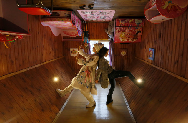 A visitor and an employee dressed as Snegurochka (Snow Maiden), the granddaughter of Ded Moroz (Russian equivalent of Santa Claus), pose for a picture inside an upside down house, constructed as an attraction for local residents and tourists and located at the Royev Ruchey Park of Flora and Fauna in the suburbs of Krasnoyarsk, Russia, December 7, 2016. (Photo by Ilya Naymushin/Reuters)