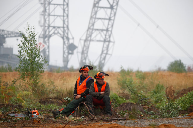 """Two lumberjacks of German utility and power supplier RWE rest on a tree stump as a brown coal excavator of the Hambach open cast mining of RWE is seen behind them next to the forest """"Hambacher Wald"""" where activists are cleared from their tree house camp by German special police forces near Kerpen-Buir next to Cologne, Germany, September 28, 2018. (Photo by Wolfgang Rattay/Reuters)"""