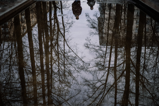 This photograph shows pedestrians reflected in a puddle on a warm spring day in Moscow on March 26, 2021. (Photo by Dimitar Dilkoff/AFP Photo)