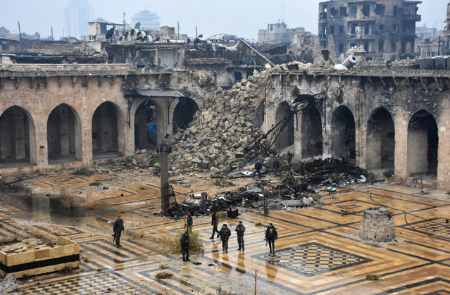 A general view shows Syrian pro-government forces walking in the ancient Umayyad mosque in the old city of Aleppo on December 13, 2016, after they captured the area. (Photo by George Ourfalian/AFP Photo)