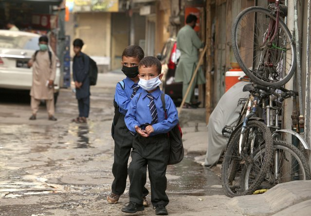 Students wear face masks to help prevent the spread of the coronavirus  in Peshawar, Pakistan, Monday, June 7, 2021. Pakistani authorities reopened educational institutes following a steady decrease in deaths and infections from the coronavirus. (Photo by Muhammad Sajjad/AP Photo)