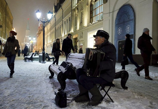 A man plays an accordion as he sits on a bench during a snowfall, in central Moscow, Russia, January 27, 2016. (Photo by Maxim Shemetov/Reuters)
