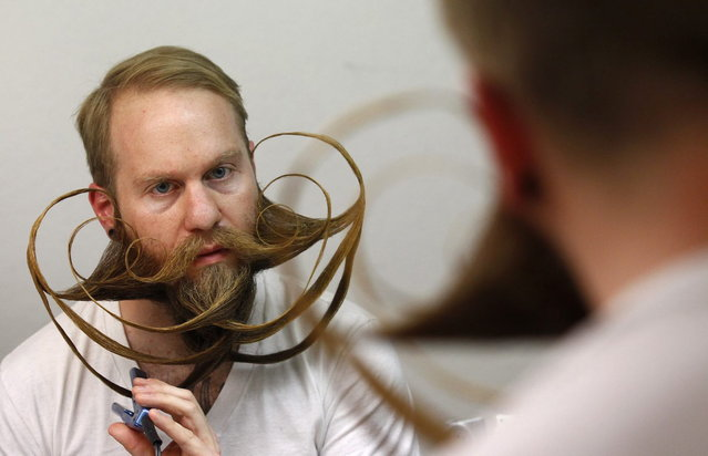 Participant Justin Kellermeier of the U.S. styles his beard for the Beard World Championship 2013 in Leinfelden-Echterdingen near Stuttgart November 2, 2013. Kellermeier needs more than 5 hours for his beard art work. More than 300 people from around the world compete in different moustache and beard categories. (Photo by Michaela Rehle/Reuters)