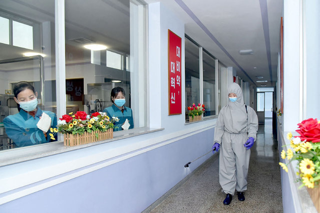 This undated picture released from North Korea's official Korean Central News Agency (KCNA) on April 6, 2021 shows employees of the Daesongsan Mineral Water Factory in Pyongyang disinfecting the facility as a quarantine measure against the new coronavirus infection. (Photo by KCNA via KNS/AFP Photo)