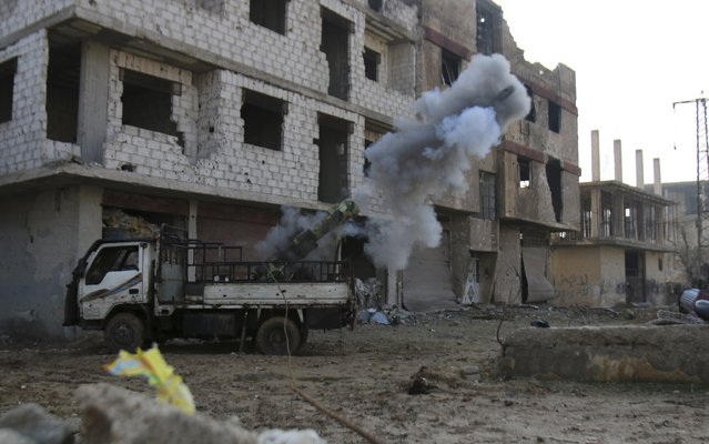 Free Syrian Army fighters launch a locally made weapon towards forces loyal to Syria's President Bashar Al-Assad from the besieged town of Arbeen in the eastern Ghouta of Damascus January 18, 2015. (Photo by Yaseen Al-Bushy/Reuters)
