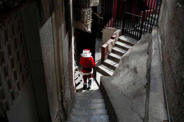 """Richard Gamboa, dressed up as Santa Claus, walks in an alley of the slum Cota 905 during the """"Santa en las calles"""" (Santa in the streets) event donating toys, food, and clothes in Caracas, Venezuela on December 1, 2018. (Photo by Marco Bello/Reuters)"""