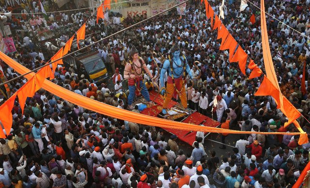 """Hindu devotees gather around giant idols of Hindu god Rama, right, and his brother Lakshman during a religious procession to mark """"Ram Navami"""" festival in Hyderabad, India, Saturday, March 28, 2015. Ram Navami celebrates the birth of Rama. (Photo by Mahesh Kumar A./AP Photo)"""