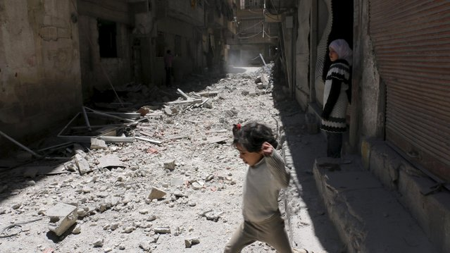 Children walk amid the rubble of collapsed buildings after what activists said was shelling by forces loyal to Syria's President Bashar al-Assad at Ain Tarma in eastern Ghouta, a suburb of Damascus, Syria April 26, 2015. (Photo by Amer Almohibany/Reuters)