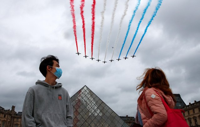 Spectators wearing protective face masks watch as Alpha jets from the French Air Force Patrouille de France fly past Pyramide du Louvre during the Bastille Day celebrations in Paris, France, July 14, 2021. (Photo by Gonzalo Fuentes/Reuters)