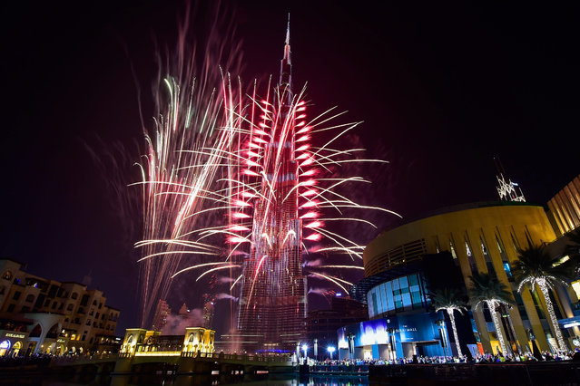 Fireworks illuminate the night sky around, the Burj Khalifa, the tallest building in the world on occasion of the new year of 2017 in Dubai, United Arab Emirates, 01 January 2017. (Photo by EPA/Stringer)