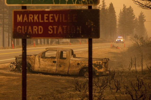 A scorched car rests on a roadside as the Tamarack Fire burns in the Markleeville community of Alpine County, Calif., on Saturday, July 17, 2021. (Photo by Noah Berger/AP Photo)