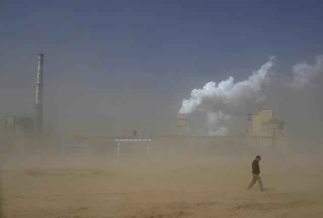 A man walks past a coal plant amidst a dust storm in Lingwu, Ningxia Hui Autonomous Region, China March 29, 2011. (Photo by Reuters/Stringer)