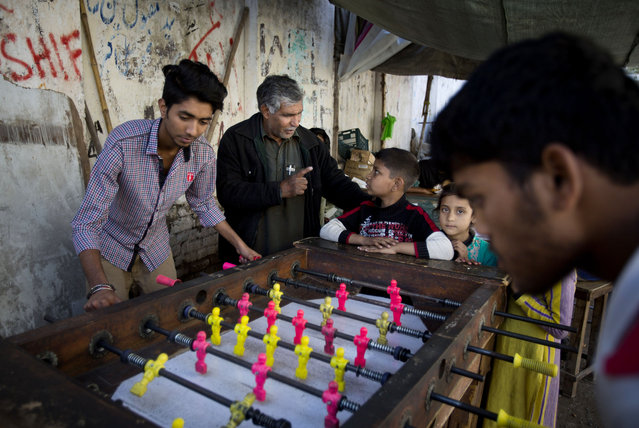 In this Wednesday, March 18, 2015 photo, Pakistan's Mohammed Ayub, second left, tries to convince children from slums, in Islamabad, Pakistan, to study at his makeshift school at the city's park. Ayub has dedicated three decades of his life to teaching underprivileged children. Now about three-quarters of his roughly 170 students go to government-run schools but some to his classes afterward for extra tutoring. (Photo by B. K. Bangash/AP Photo)