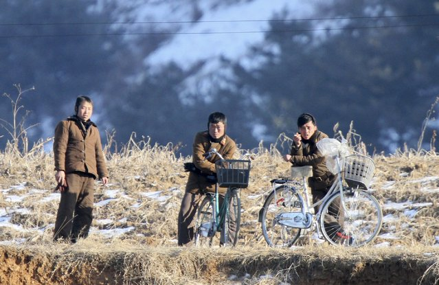 Members of North Korean military rest on their bicycles on the banks of Yalu River, in Sakchu county, North Korea, January 7, 2016. (Photo by Jacky Chen/Reuters)