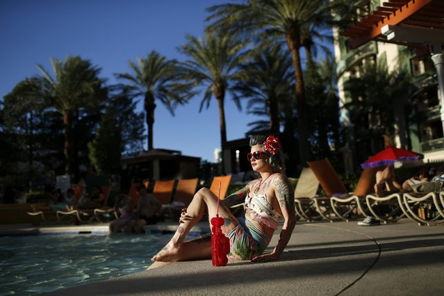 In this April 4, 2015, photo, a woman who goes by Martha War sits by the pool during the Viva Las Vegas Rockabilly Weekend in Las Vegas. Thousands of rockabilly fans attended the 18-year-old even. (Photo by John Locher/AP Photo)