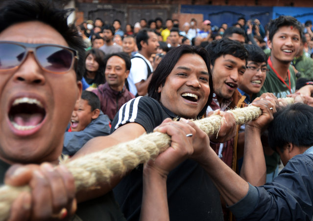 Nepalese Hindu devotees pull a wooden chariot as they take part in Bisket Jatra, a festival held in celebration of the Nepalese New Year in Bhaktapur, some 12 kms east of Kathmandu on April 10, 2015. The festival, which began April 10, is celebrated for nine days by the ethnic Newar community in Bhaktapur. (Photo by Prakash Mathema/AFP Photo)
