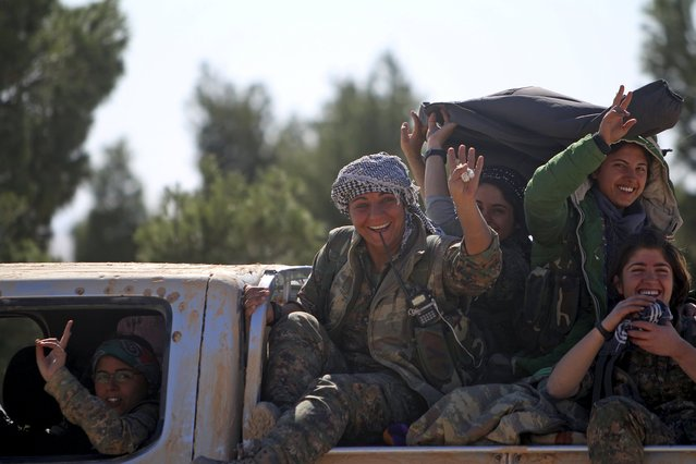 Democratic Forces of Syria women fighters gesture while riding a pick-up truck near al-Shadadi town, Hasaka countryside Syria February 18, 2016. (Photo by Rodi Said/Reuters)