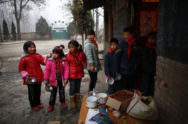 Students line up outside the school kitchen as they wait for dinner at the Democracy Elementary and Middle School in Sitong town, Henan province December 3, 2013. (Photo by Carlos Barria/Reuters)