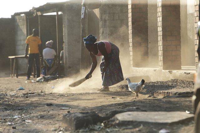 A woman sweeps outside her house in Lusaka, Zambia, Saturday, August 14, 2021. (Photo by Tsvangirayi Mukwazhi/AP Photo)