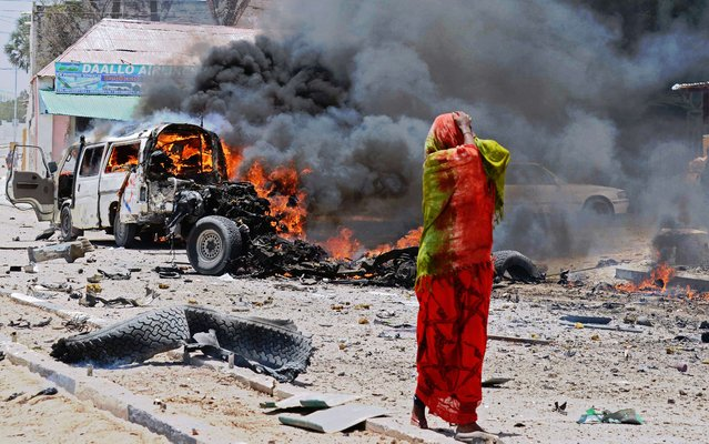 A Somali woman reacts on March 18, 2013 near the site of a car bomb in central Mogadishu. (Photo by Mohamed Abdiwahab/AFP Photo)