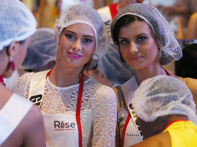 Miss Universe contestants Johanna Acs, left, of Germany and Barbara Filipovic of Croatia, pose as they help in packing meals for the needy in suburban Pasay city southeast of Manila, Philippines Wednesday, January 18, 2017. (Photo by Bullit Marquez/AP Photo)