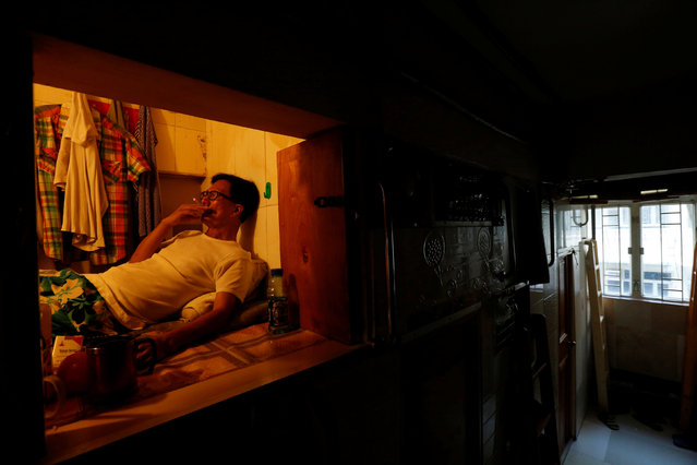"""Unemployed Hong Kong resident Simon Wong, 61, smokes inside his 4-by-6-feet partitioned unit, or """"coffin unit"""", with a monthly rent of HK$1,750 ($226) in Hong Kong, China October 31, 2016. (Photo by Bobby Yip/Reuters)"""