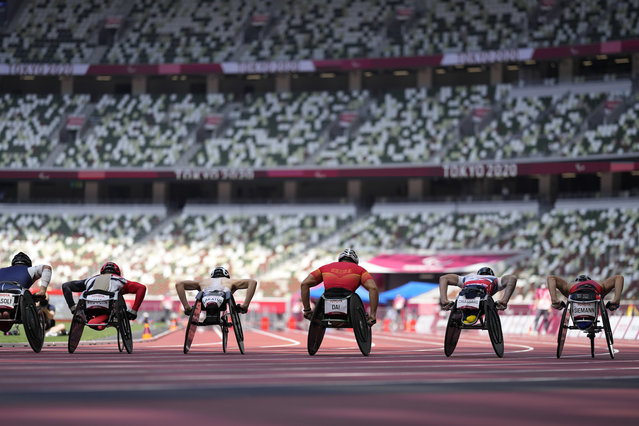 Athletes compete during the men's 1500m T54 heats in front of empty stands in the 2020 Paralympics at the National Stadium in Tokyo, Monday, August 30, 2021. (Photo by Eugene Hoshiko/AP Photo)