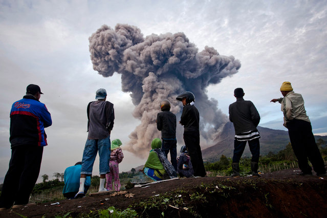 People watch as Mount Sinabung spews pyroclastic smoke on January 8, 2014 in Karo District, North Sumatra, Indonesia. (Photo by Ulet Ifansasti/Getty Images)