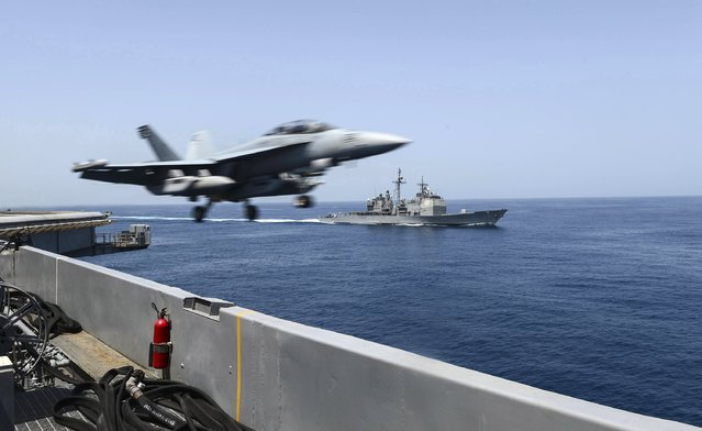 An EA-18G Growler launches from the flight deck of the aircraft carrier USS Theodore Roosevelt (CVN 71) with the guided-missile cruiser USS Normandy (CG 60) alongside during maritime security operations in the Arabian Sea in this U.S. Navy photo taken April 21, 2015. (Photo by Mass Communication Specialist 3rd Class Josh Petrosino/Reuters/U.S. Navy)