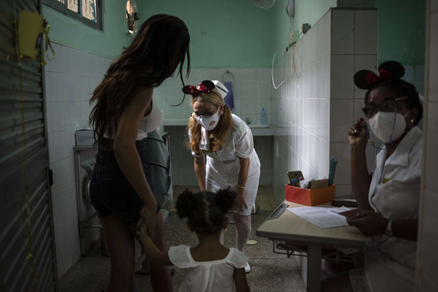 A nurse greets a young girl as she arrives with her mother to receive a dose of the Soberana-02 COVID-19 vaccine, in Havana, Cuba, Thursday, September 16, 2021. Cuba began inoculating children as young as 2-years-old with locally developed vaccines on Thursday. (Photo by Ramon Espinosa/AP Photo)