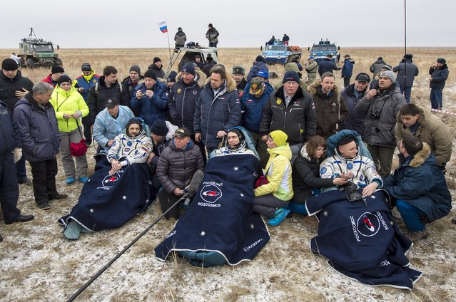 U.S. astronaut Scott Kelly (R) and Russian cosmonauts Sergei Volkov (C) and Mikhail Korniyenko, surrounded by ground personnel, rest shortly after landing near the town of Dzhezkazgan (Zhezkazgan), Kazakhstan, March 2, 2016. (Photo by Bill Ingalls/Reuters/NASA)