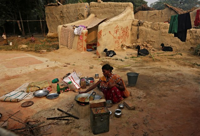 A woman prepares breakfast outside her house in Jogi Dera (snake charmers settlement), in the village of Baghpur, in the central state of Uttar Pradesh, India November 10, 2016. (Photo by Adnan Abidi/Reuters)