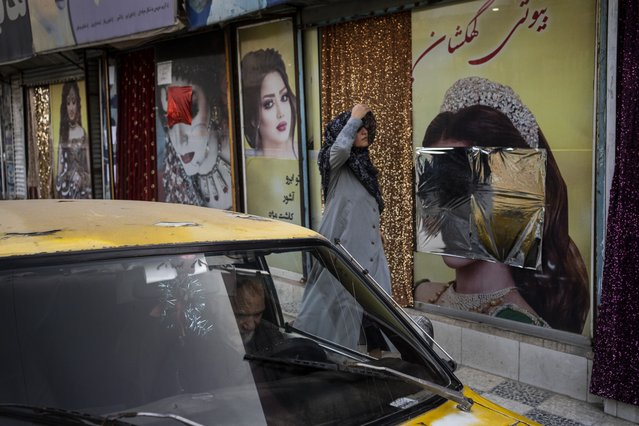 An Afghan woman walks past beauty salons with defaced window decorations, in Kabul, Afghanistan, Sunday, September 12, 2021. Since the Taliban gained control of Kabul, several images depicting women outside beauty salons have been removed or covered up. (Photo by Bernat Armangue/AP Photo)