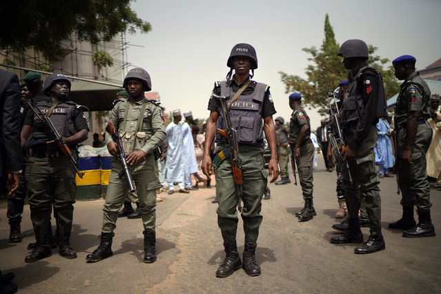 Nigerian police guard the entrance of the All Progressives Congress (APC) party headquarters where Incumbent President Muhammadu Buhari holds an emergency meeting with senior members of the party in Abuja, Nigeria, Monday February 18, 2019. Nigeria's electoral commission delayed the presidential election until Feb. 23. (Photo by Jerome Delay/AP Photo)