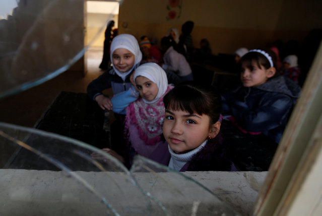 Schoolchildren react to the camera through a window as they attend class after registering in school in Mosul, Iraq, January 23, 2017. (Photo by Muhammad Hamed/Reuters)