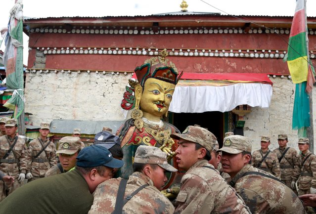 Soldiers of People's Liberation Army (PLA) remove a religious statue from a damaged lamasery after a 7.9-magnitude earthquake hit Nepal on Saturday, in Nyalam county, Tibet Autonomous Region, China, April 28, 2015. (Photo by Reuters/China Daily)
