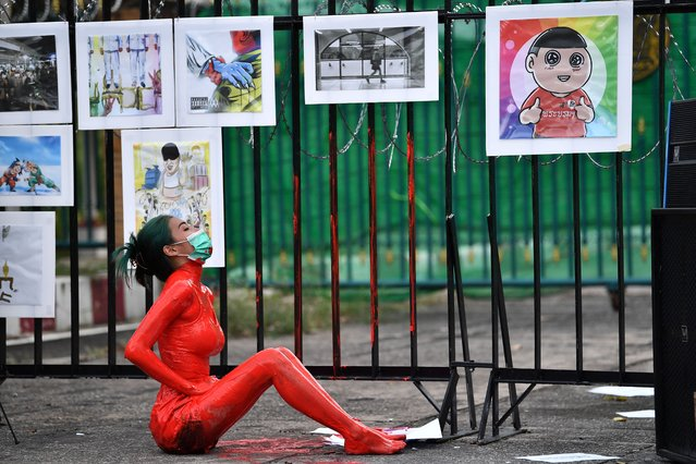 A protester is covered in red paint during a demonstration against the government of Thailand's Prime Minister Prayut Chan-O-Cha and in support of the release of political prisoners outside Bangkok Remand Prison in Bangkok on October 13, 2021. (Photo by Lillian Suwanrumpha/AFP Photo)