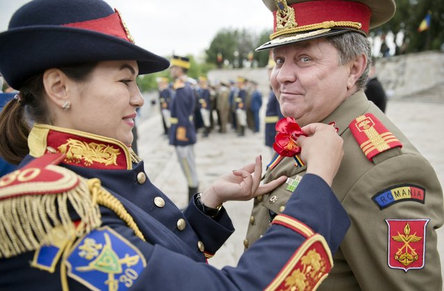 A Romanian serviceman has a flower pinned to his uniform by an Honor Guard soldier at the WWII Heroes monument in Bucharest, Romania, Wednesday, April 29, 2015. Romania's armed forces held a ceremony to celebrate WWII Veterans Day, marking 70 years since the end of WWII. (Photo by Vadim Ghirda/AP Photo)