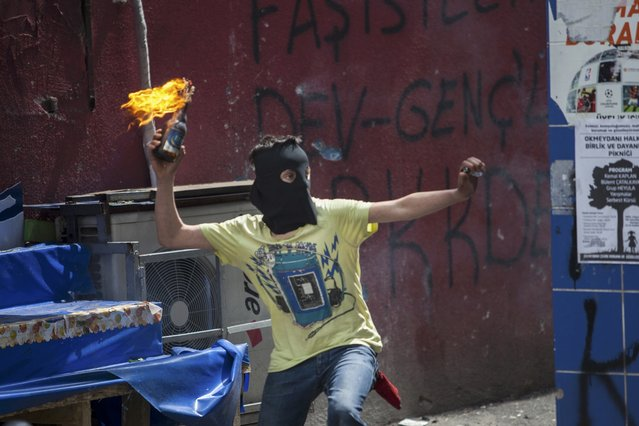 A masked protester prepares to throw a Molotov cocktail during clashes with police in Okmeydani neighbourhood in Istanbul, Turkey, May 1, 2015. (Photo by Kemal Aslan/Reuters)
