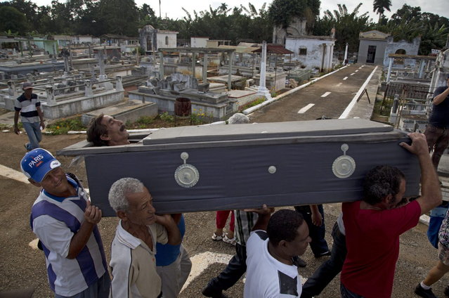In this February 5, 2014 photo, Divaldo Aguiar, who plays the part of Pachencho, is carried in a mock coffin during the Burial of Pachencho celebration, through a cemetery in Santiago de Las Vegas, Cuba. Cuban villagers stage a mock funeral and burial of Pachencho, with a living man playing the part of Pachencho, in a boozy festival that has become an annual tradition in this small town near Havana, held each February 5 for the last 30 years. (Photo by Enric Marti/AP Photo)