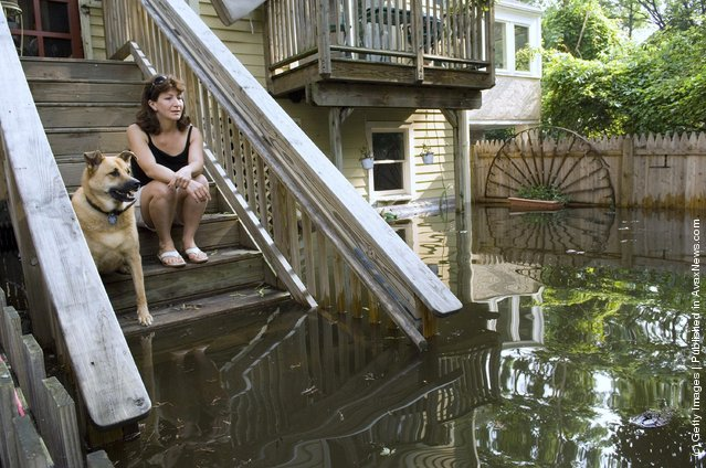 Patty Yardley and dog Bailey sit on the rear steps of their Ferry Street home and watch as floodwaters from the Delaware and Raritan Canal and Delaware River continue to rise June 29, 2006 in Lambertville, New Jersey