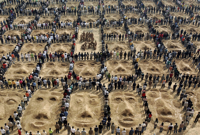 College students stand around sculptures during an art performance in Zhengzhou, central China's Henan province March 27, 2007. (Photo by Reuters/China Daily)